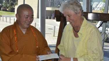 Shaolin Abbot Shi Yongxin presents a bank cheque to Shoalhaven Mayor Joanna Gash for $4,162,723.99 to finalise the mortgage payments for his $380m NSW complex.
