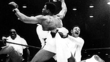 In this Feb. 25, 1964, file photo with flailing arms and legs, new heavyweight boxing champion Cassius Clay is lifted off the ring floor in Miami Beach by one of his handlers when Sonny Liston was unable the answer the bell for the seventh round.