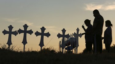 Irene and Kenneth Hernandez and their daughter Miranda Hernandez say a prayer on Monday, in front of some of the crosses placed in a field in Sutherland Springs.