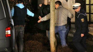 A person covered with a black blanket is led by police officers from the Lubitz family house in Montabaur on Thursday.