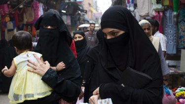 Indian Muslim women walk at a market area in Delhi, India.