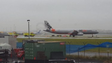 Fire trucks drive to meet a Jetstar flight that was turned back to Sydney Airport on Sunday afternoon.