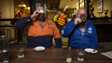 Construction workers Ron Horn and David Jones enjoy early morning coffee at Spriga Espresso Bar on King Street, Melbourne.