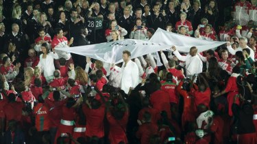 Ian Thorpe carries the Commonwealth Games flag.