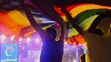 """Image of two people holding up a rainbow flag at a concert in Cairo, Egypt Security officials said those arrested have been charged with """"inciting immorality""""."""
