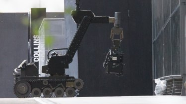 A bomb squad robot investigating the package that turned out to be a pair of shoes.