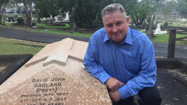 Historian Peter Collins at Canon Garland's grave at Toowong Cemetery.