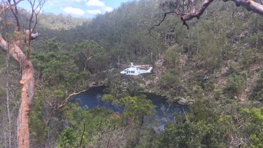 A helicopter winches a 16-year-old boy to safety after he collapsed on a beach at the Georges River.