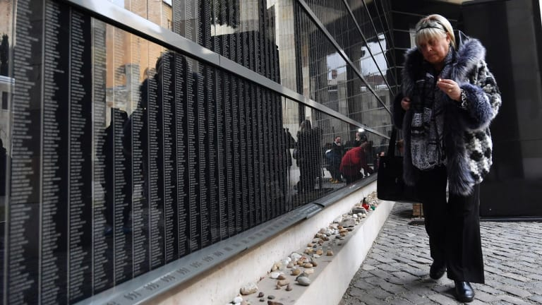 Holocaust survivor Katalin Sommer lights a candle at the Victims' Memorial Wall in the Holocaust Memorial Centre in Budapest, Hungary. This year is the 70th anniversary of the liberation of the Auschwitz concentration camp.