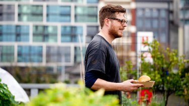 Raphael Guthrie from Burn City Smokers takes a burger to a fellow veggie grower at Pop Up Patch.