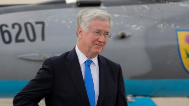Britain's Defence former Minister Michael Fallon walking next to a Soviet era built MIG21 jet fighter at the Mihail Kogalniceanu air base, Romania in June.
