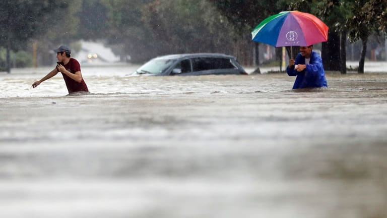Moses Juarez and Anselmo Padilla wade through floodwaters Houston, Texas on Sunday.