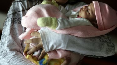 A teen girl holds her one-month-old baby at a shelter for troubled children in Ciudad del Este, Paraguay in May.
