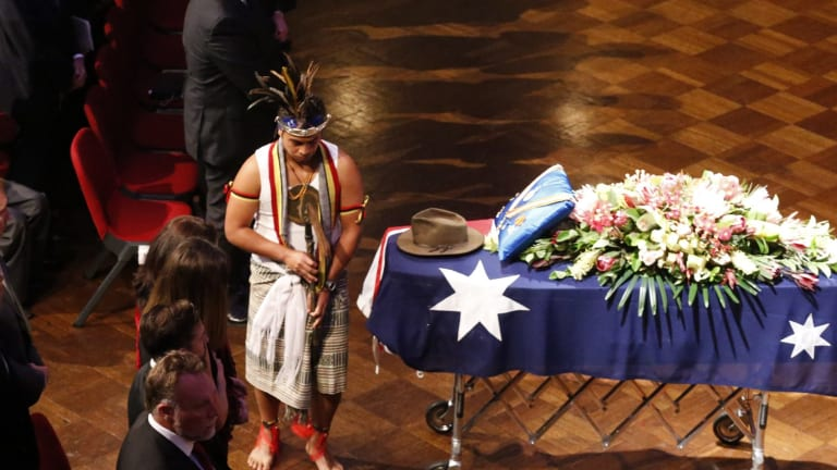 An East Timorese ceremonial dancer alongside Uren's decorated casket at the Town Hall.