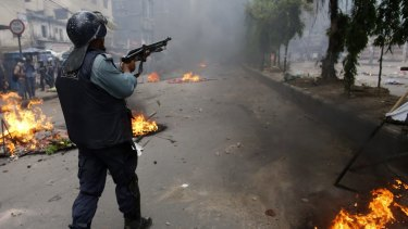 A police officer shoots rubber bullets during a clash with Islamic activists in Dhaka in 2013: the government has tried to crack down on hardline Islamist groups.
