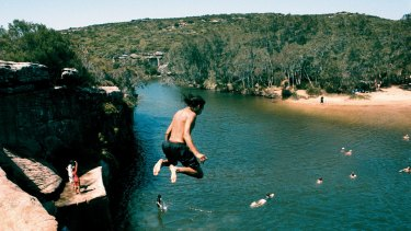 Kids jumping off rocks into Wattamolla lagoon.