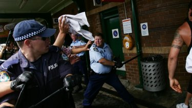 Campbell swings his baton in what would become an iconic photo from the Cronulla riots.