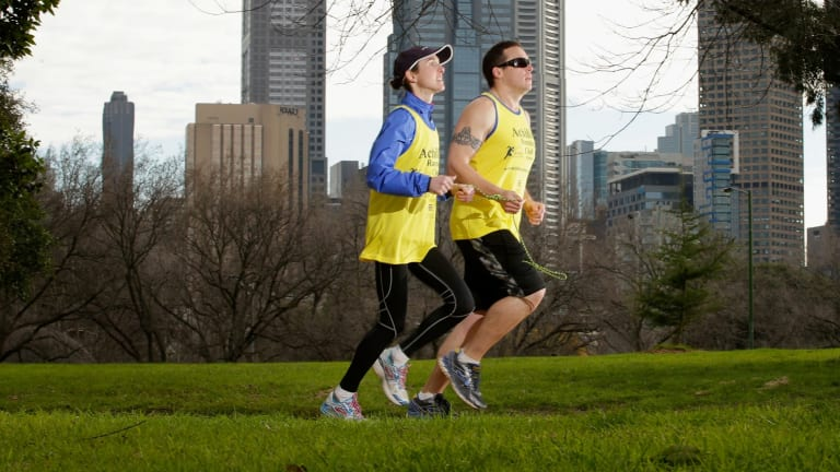 Adam Koops, who is blind, trains on Sundays with Achilles Running Club volunteer Amelia Griffith around the Tan running track around Melbourne's Royal Botanic Gardens.