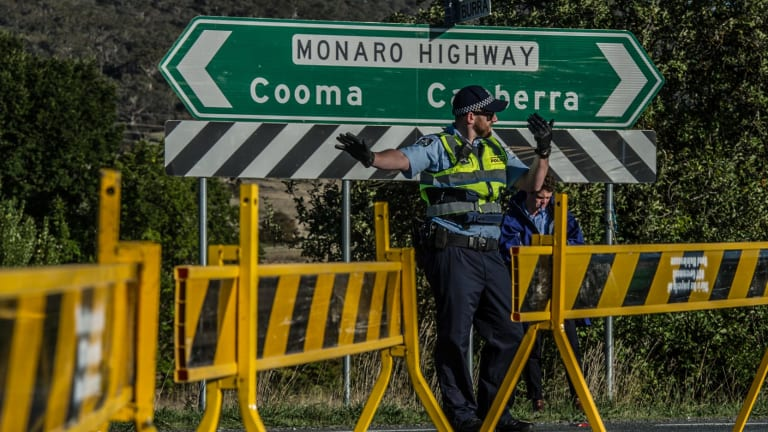 ACT Police conduct road traffic management near the scene of the fatal accident involving a cyclist and a car on the Monaro Highway.
