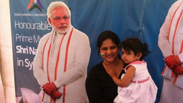 Members of the Indian community pose with a cutout of Narendra Modi at Homebush on Monday.