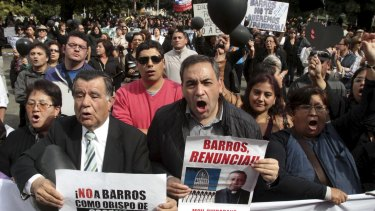 Politician Fidel Espinoza, right, and fellow Chileans protest as Bishop Juan Barros conducts his first service as bishop in Osorno cathedral, south of Santiago.