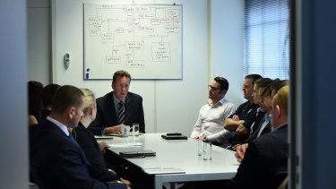 Andrew Donoghoe briefs members of his AFP team inside the Australian embassy in The Hague.