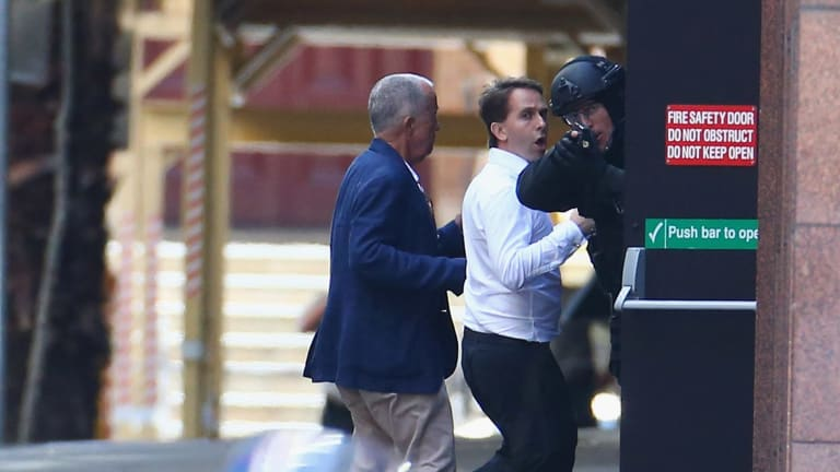 Two hostages run to safety outside the Lindt cafe.