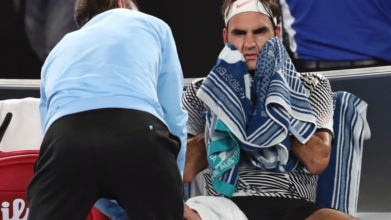 Roger Federer receives treatment from trainer during his men's singles final against Rafa Nadal.