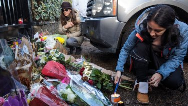 A woman lights a candle as tributes of flowers are left at the home of the pop music icon.