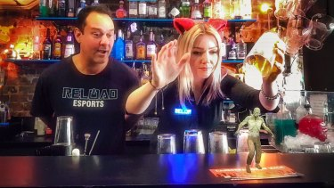 Reload Bar co-owner Ravi Sharma watches manager Hollie Lehmann attempt to catch a zombie with a beer glass in Australia's first augmented reality bar. The scene is photographed on a phone using the bar's app.