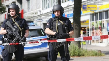 Police officers secure the area after a knife attack at a supermarket in Hamburg on Friday.