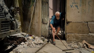 Abdulsalam Abdulqadir, 73, sweeps outside his gate from his wheelchair at the entrance of his home in West Mosul, Iraq.