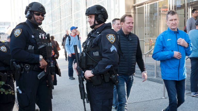 New York City police stand guard outside the Jacob Javits Convention Centre as runners arrive to register for Sunday's New York City Marathon.