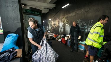Nigel Blakemore, who had been living in Martin Place, cleans up belongings after the City of Sydney removed the homeless camp.