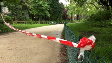 White-and-red tape is strung across a pathway through Parc Monceau after the lightning strike.