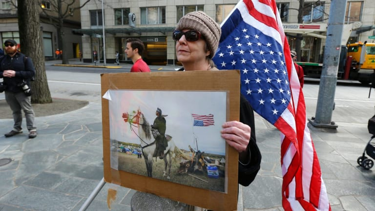 Dianne Reeves, of Seattle, holds an upside-down U.S. flag, commonly seen as a sign of distress, and a photo from the Standing Rock oil pipeline protests, in Seattle.