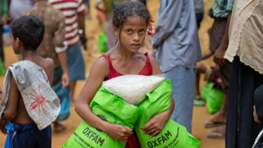 A newly arrived Rohingya girl carries bags of food rations in Kutupalong, Bangladesh.