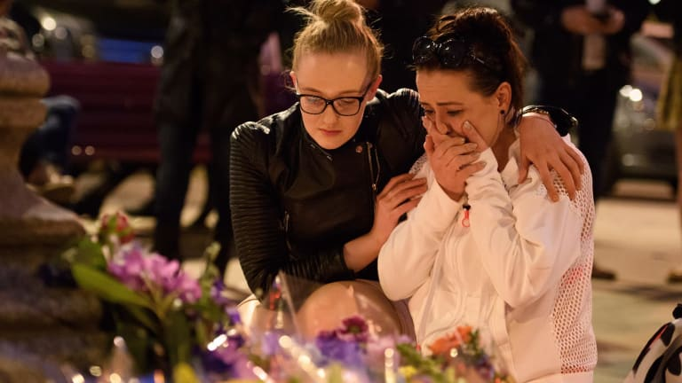 A woman is consoled as she looks at the floral tributes following an evening vigil outside the Town Hall in Manchester.