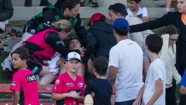 A boy is treated after being hit by a ball during the Women's Big Bash League cricket match between the Sydney Sixers and the Melbourne Stars at North Sydney Oval on Saturday.