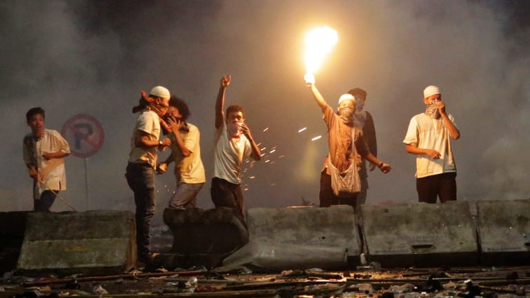 A protester holds up a blowtorch during a clash with police outside the presidential palace in Jakarta.