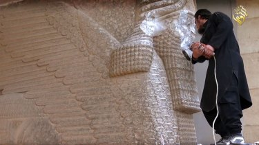 An Islamic State militant destroys the statue of Lamassu, an Assyrian deity, with a jackhammer in the northern Iraqi Governorate of Nineveh.