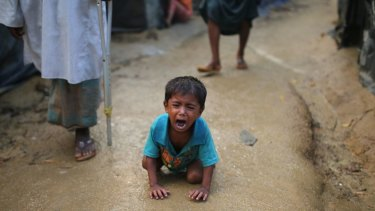 A Rohingya child cries kneeling on the ground at a makeshift camp near Kutupalong refugee camp in Cox's Bazar, Bangladesh.