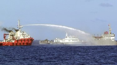 A Chinese ship sprays water on a Vietnamese vessel, right, while a Chinese Coast Guard ship, centre, sails alongside in the South China Sea in May 2014.