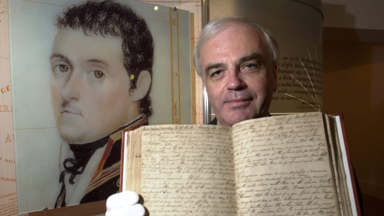 Paul Brunton, curator of the State Library of NSW holds up Flinder's logbook at The National Archives in 2003.