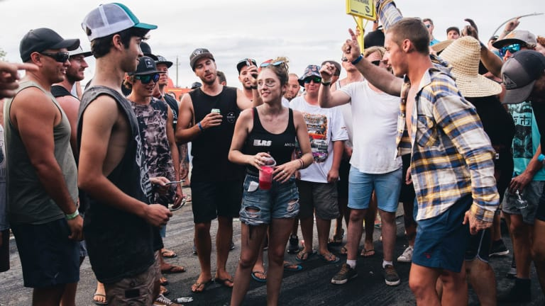 A group of men surround a young woman and shout 'black top, black top' requesting she remove her top. She didn't remove her top.