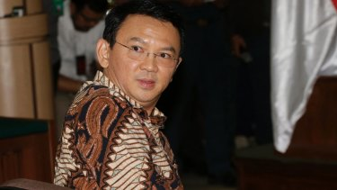 Jakarta governor Ahok sits on the defendant's chair at the start of his trial.
