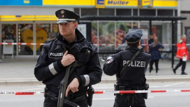 Police officers secure the area after the knife attack at a supermarket in Hamburg.