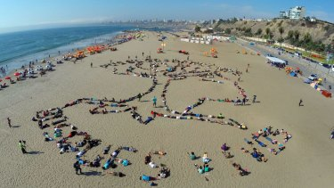 On Agua Dulce beach in Lima, native Peruvian activists formed an indigenous symbol and the words 'People and rights. Alive woods' to call attention to climate change.