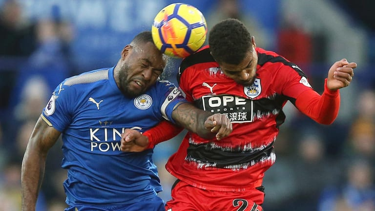 Leicester City's Wes Morgan, and Huddersfield Town's Steve Mounie clash at the King Power Stadium.