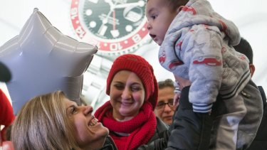 Tima Kurdi, left, who lives in the Vancouver area, lifts her five-month-old nephew, Sherwan Kurdi, after her brother, Mohammad Kurdi, and his family, arrive in Canada as refugees.